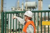 Eletricista indica ao transformador perto da subestação elétrica — Foto Stock