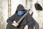 Man with a machete leaning against old wall — Stock Photo