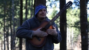 Man playing guitar in the woods leaning against tree episode one — Stock Video