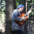 Man playing guitar in the woods leaning against tree episode three — Stock Video #25244193