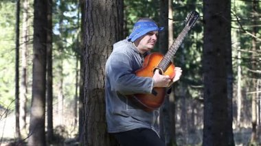Man playing guitar in the woods leaning against tree episode two — Stock Video