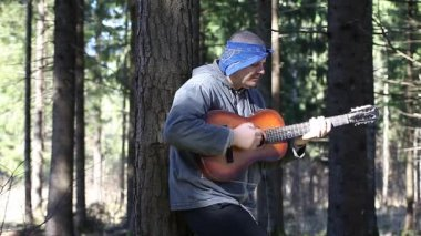 Man playing guitar in the woods leaning against tree episode four — Stock Video