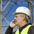 Engineer talking on the cell phone near to gsm tower — Stock Photo