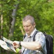 Hiker in the woods on trails staring at the clock — Stock Photo