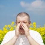 Man sneezes on canola field — Stock Photo #25576017