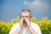 Man sneezes on canola field — Stock Photo