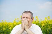 Man keep hands near nose on canola field — Stockfoto