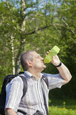 Hiker drinking water from bottle on forest trails — Stock Photo