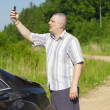 Foto Stock: Mwith cell phone on country road to car