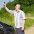 图库照片: Mwith cell phone on country road to car