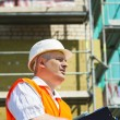 Stock Photo: Construction Manager with folder at scaffolding near new building