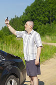 Man with the cell phone on the country road to the car — Stock Photo