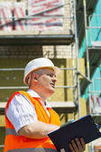 Construction Manager with folder at the scaffolding near new building — Stock Photo