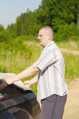 Man with the map on the country road to the car — Stock Photo