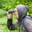 Stock Photo: Mwith binoculars watching birds at lake
