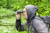 Man with binoculars watching birds at the lake — Stock Photo