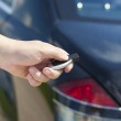 Hand with a car alarm remote control at the back of the car — Stock Photo