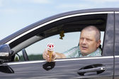 Man sitting in a car offers ice cream — Stock Photo