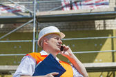 Construction Manager talking on the phone near the scaffolding — Stock Photo