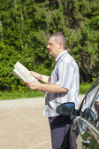 Man with the map on the rural intersection near the car — Stock Photo