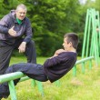 Father and son engaged in athletic exercises — Stock Photo