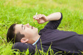 Boy with a cigarette lying in a meadow — Stock Photo