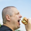 Man starting eat burger on a blue sky background — Stock Photo #26882289