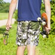 Stock Photo: Boy with a slingshot and skateboard on rural road