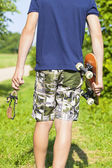 Boy with a slingshot and skateboard on rural road — Stock Photo