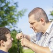 Angry man with slingshot in hand against the boy — Stock Photo