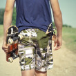 Stock Photo: Boy with skateboard and slingshot in pocket on rural road in summer