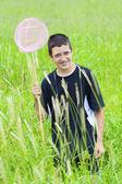 Glimlachend jongen vangen vlinders in de weide — Stockfoto