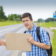 Boy hitchhiker on the road waiting for car to stop — Stock Photo