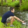 Stock Photo: Boy with paper boat near river