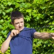 Stock Photo: Boy with a slingshot near the bush