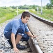 Boy puts stones on railway tracks — Stock Photo