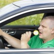 Man in car with yellow lollipop — Stock Photo