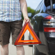 Man with warning triangle near car on the road — Stock Photo