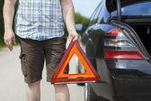 Hombre con triángulo de advertencia cerca de un coche en la carretera — Foto de Stock