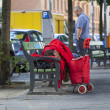 Homeless sleeping on a bench in the street — Stock Photo