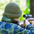 Man with optical rifle in the woods — Stock Photo