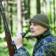 Man with optical rifle and binoculars in the woods — Stock Photo