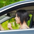 Woman with the lipstick in the car — Stock Photo