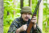 Cacciatore con fucile ottico nel bosco — Foto Stock
