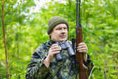 Hunter with optical rifle and binoculars in the woods — Stock Photo