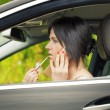 Woman with the lipstick and cell phone in the car — Stock Photo