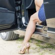 Woman stepping out of the car to rural road — Stock Photo