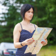 Woman with map on the rural road — Stock Photo