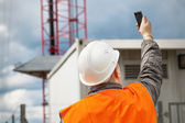 Engineer with the cell phone near to gsm tower — Stock Photo