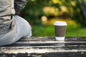 Man with coffee on a bench in the park — Stock Photo